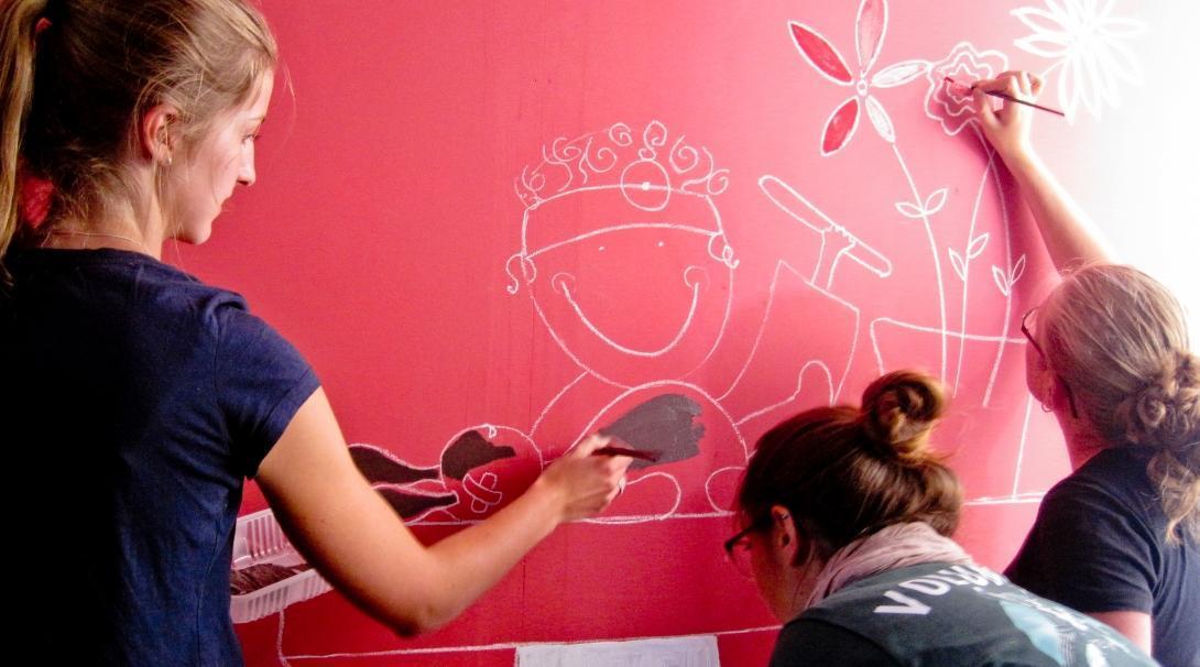 Voluntarias trabajando con niños en Argentina ayudan a pintar un mural didáctico.